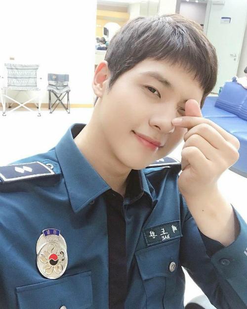 CNU (B1A4) đốn tim fan khi mặc đồng phục cảnh sát, tạo dáng bắn tim.
