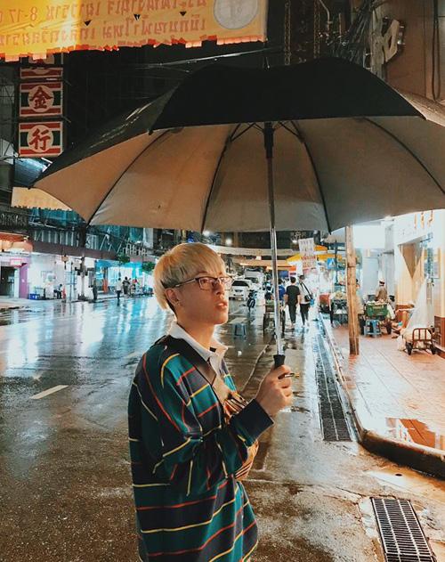 Đức Phúc đứng giữa đường phố Thái Lan diễn sâu để có kiểu ảnh mơ màng lúc trời mưa.