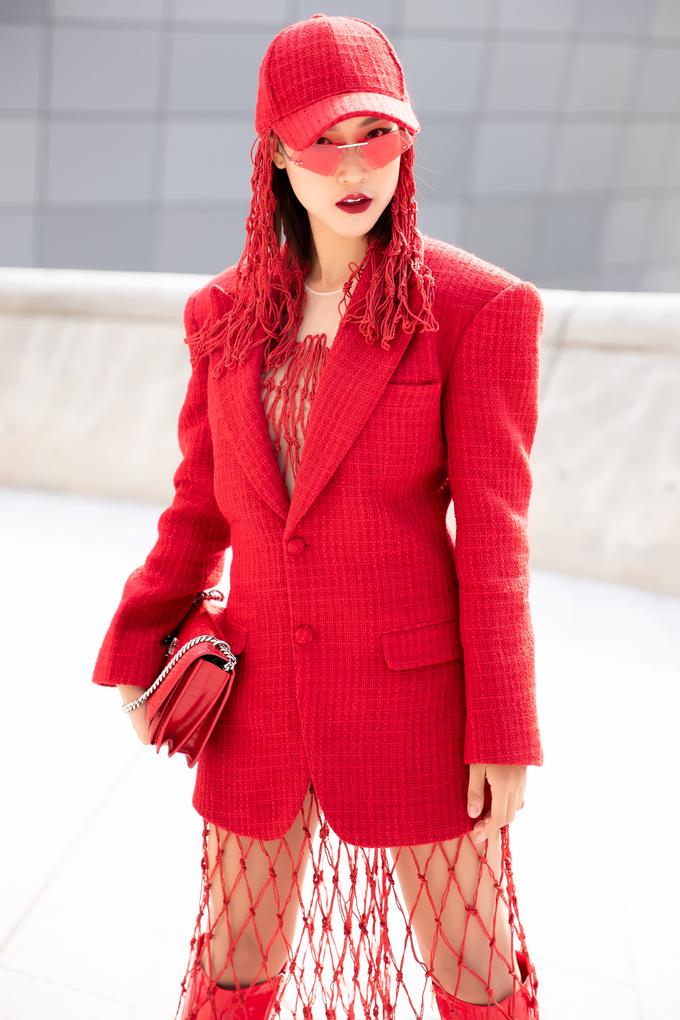 """<p> Cô chọn """"cây đỏ"""" chứng minh độ fashionista đích thực. Set đồ của Hoàng Oanh sử dụng phần áo vest đỏ form dáng rộng đi kèm với phần váy lưới để dễ dàng khoe đôi boots cùng màu.</p>"""