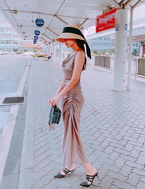 Midu ra sân bay mà diện đồ lồng lộn chẳng khác gì đi tiệc, Cô nàng mặc váy lụa nhún eo, kết hợp mũ cói đội sùm sụp kiểu tiểu thư.