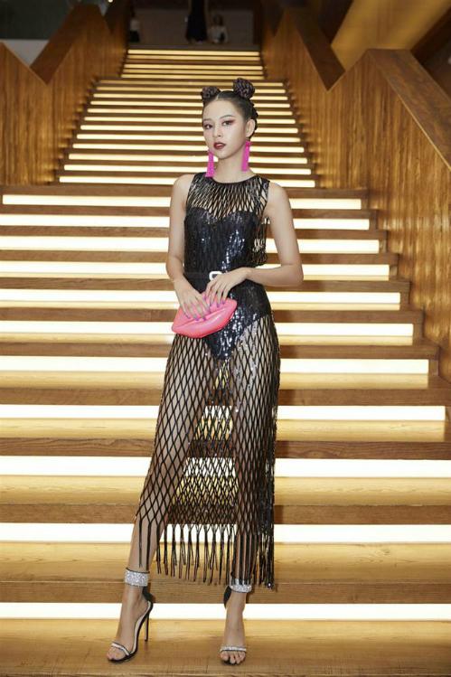 Phí Phương Anh phối bộ đồ lưới đính sequin cùng khuyên tai tua rua gam màu hồng cánh sen và túi xách tiệp màu. Ngoài ra, người mẫu sinh năm 1996 cũng chọn cách búi tóc xoắn thừng tinh nghịch, tạo điểm nhấn tại sự kiện.