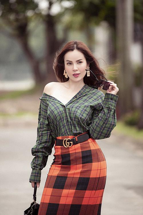 Người đẹp hô biến chiếc ao sơmi bình thường trở thành chiếc áo trể nải kết hợp với chiếc váy cam carô mix cùng chiếc túi Chanel.