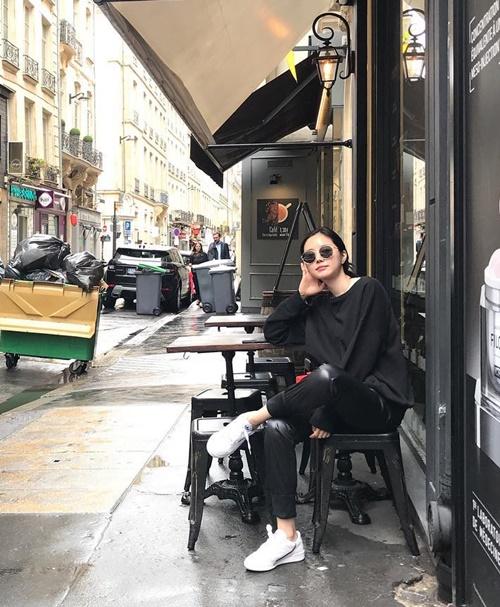 Na Eun diện đồ đen sành điệu ngồi vắt chân ở quán bên đường.