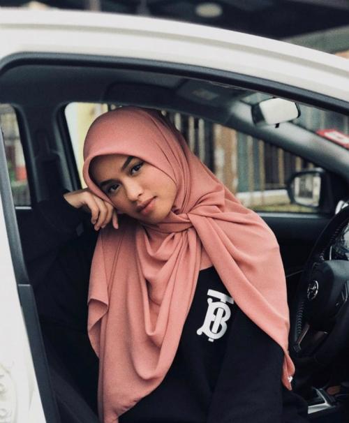 Fashionista nổi tiếng người Malaysia - Syasya bắt kịp xu hướng khi phối chiếc áo thun đơn giản cùng khăn quấn truyền thống.