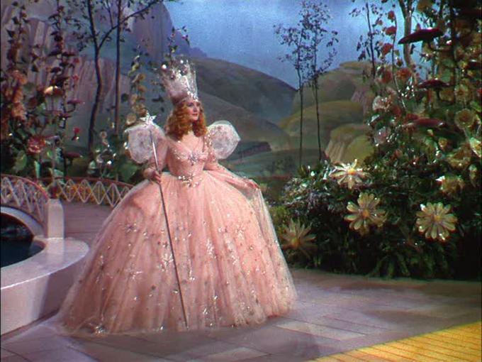 """<p> Bên cạnh đôi giày ruby đế thấp và bộ váy kẻ màu xanh da trời """"bất hủ"""" mà nữ diễn viên Judy Garland diện trong bộ phim<em>Phù thủy xứ Oz</em>(1939), bộ váy dạ hội màu hồng lấp lánh của phù thủy Glinda (Billie Burke) cũng trở thành một trong những outfit được cosplay """"điên đảo"""" của khán giả nhiều thế hệ.</p>"""
