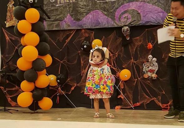 Cô bé tự tin đứng trên sân khấu với tạo hình dễ thương.