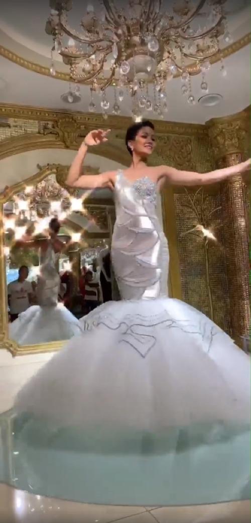 Xuất hiện trong mộtbuổi thử trang phục dạ hội, Hoa hậu HHen Niê chia sẻ khoảnh khắc lộng lẫy trên trang cá nhân. Trong clip, cô diện bộ đầm lệch vai ôm sát cơ thể, kiểu dáng đuôi cá, gam màu ánh kimnổi bật.