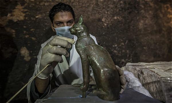 Một nhà khảo cổ làm sạch một bức tượng mèo cổ.Người Ai Cập cổ đại tôn thờ mèo như các vị thần. Ảnh:AFP