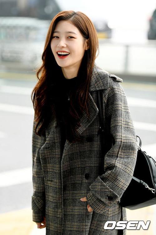 Chae Yeon trung thành với hình tượng thơ ngây, mái tóc xoăn nhẹ đầy nữ tính. Cô nàng kết hợp balo nhỏ trẻ trung, áo khoác dài kẻ hợp xu hướng trong set đồ sân bay.