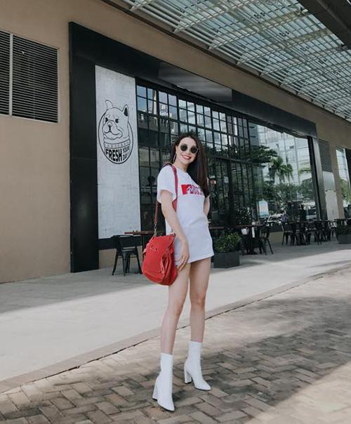 Chiếc áo phông H&M x Moschino được Trà Ngọc Hằng biến thành váy ngắn, kết hợp boots trắng cùng tông tôn lên đôi chân thon dài.
