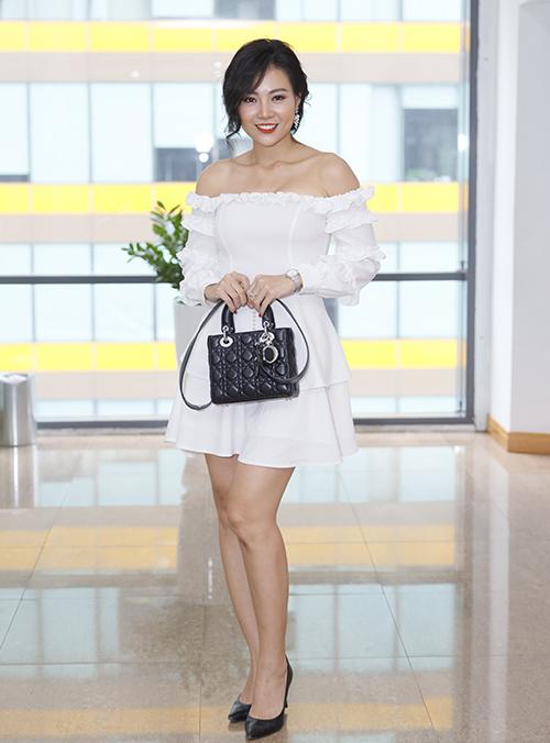 Thanh Hương diện đầm trễ vai trắng tôn lên vòng một gợi cảm, kết hợp cùng túi xách Dior.