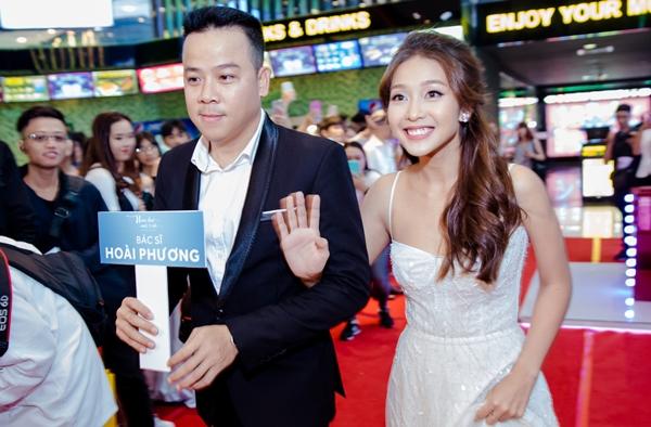 Khả Ngân khoác tay đạo diễn phim Trần Bửu Lộc xuất hiện trong tiếng reo hò của fan.