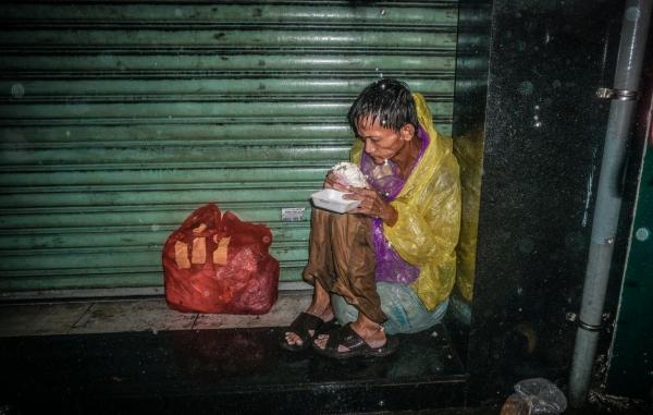 Ảnh người đàn ông vô gia cư co ro trong đêm mưa lớn Sài Gòn gây xúc động