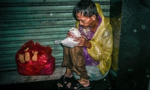 Ảnh người vô gia cư co ro trong đêm mưa lớn ở Sài Gòn gây xúc động