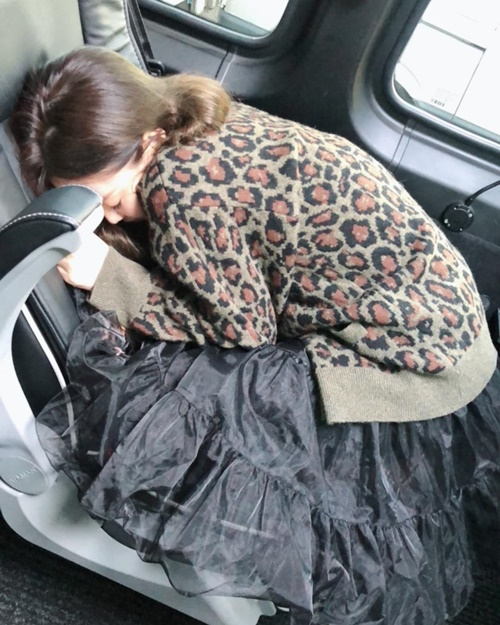 Jennie nằm co trên chiếc ghế ô tô nghỉ ngơi với dáng vẻ vừa đáng yêu vừa tội nghiệp.