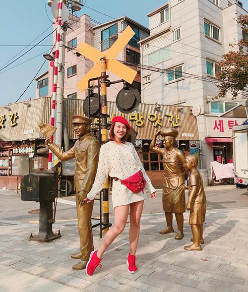 Hoàng Oanh diện áo len giấu quần và cả cây phụ kiện đỏ nổi bần bật trên đường phố Hàn Quốc.