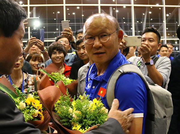 Thầy trò HLV Park Hang-seo được tặng hoa ở sân bay. Nhiều người hâm mộ cũng nhận ra đội bóng của Việt Nam.