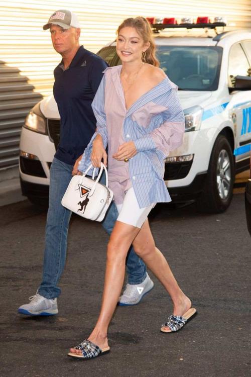 Khác với tiên nữ cử tạ, Gigi Hadid mặc chiếc áo sơ mi oversize giống hệt xuống phố. Siêu mẫu kết hợp item này cùng quần short ngắn và dép bệt.