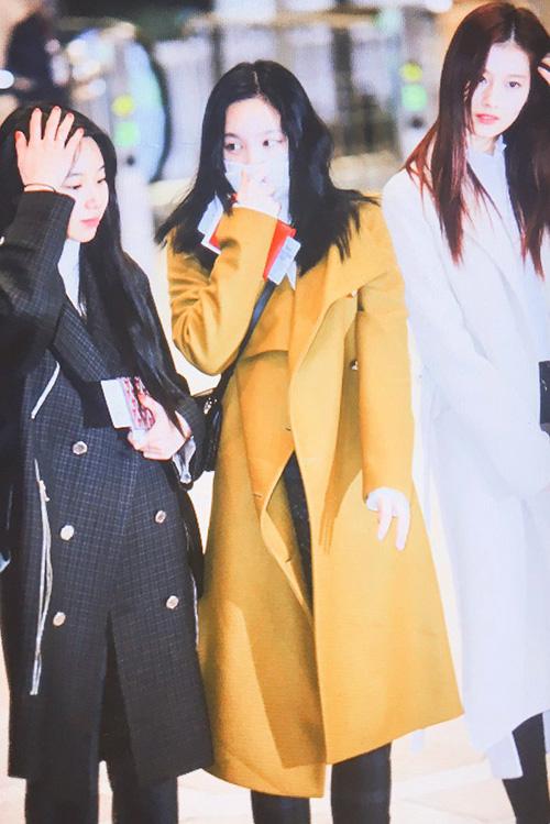Na Yeon (áo vàng) khiến fan lo lắng khi liên tục che mặt, cúi đầu ở sân bay.