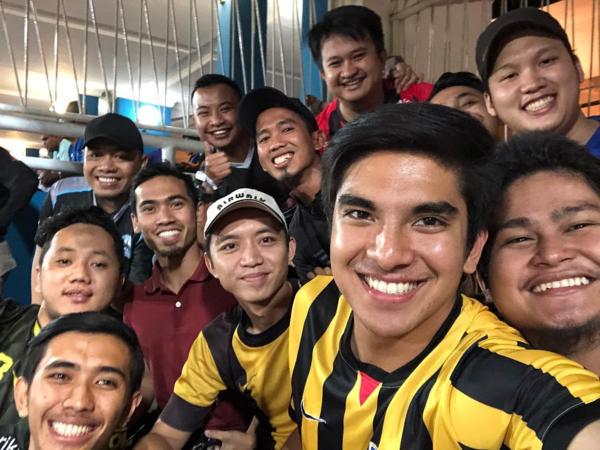 Bộ trưởng Thanh niên và Thể thao Malaysia Syed Saddiq mặc áo tuyển thi đấu chụp ảnh cùng với những CĐV khác.Ảnh: Malay Mail