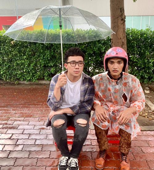 Trấn Thành ngồi che ô cho bản thân, bỏ mặc anh bạn Mạc Văn Khoa bên cạnh phải mặc áo mưa, đội mũ bảo hiểm.