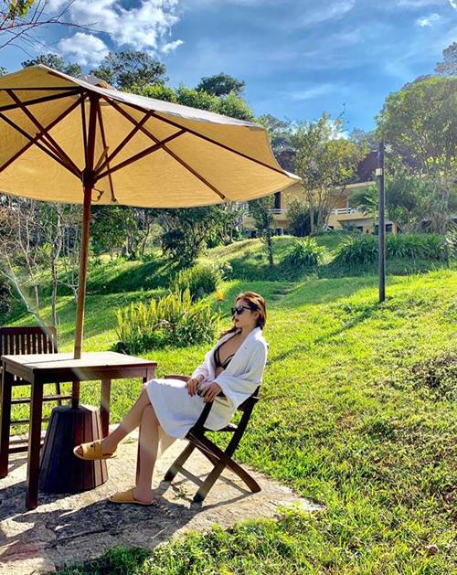 Kỳ Duyên diện bikini nửa kín nửa hở ngồi tắm nắng trong một khu resort.