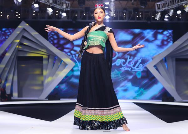 Siêu mẫu Khả Trang đi chân trần, nổi bật trong sari truyền thống của Ấn Độ. Bằng kinh nghiệm nhiều năm trên sàn diễn, người đẹp hoàn thành phần catwalk với nhiều cú xoay người ấn tượng. Siêu mẫu còn thể hiện khéo léo động tác múa của người Ấn khiến khán giả thích thú.