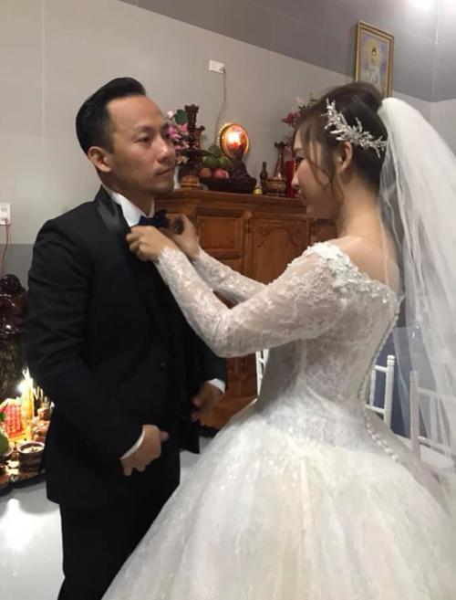 Cô dâu đang chỉnh trang phục cho chú rể trước giờ làm lễ.