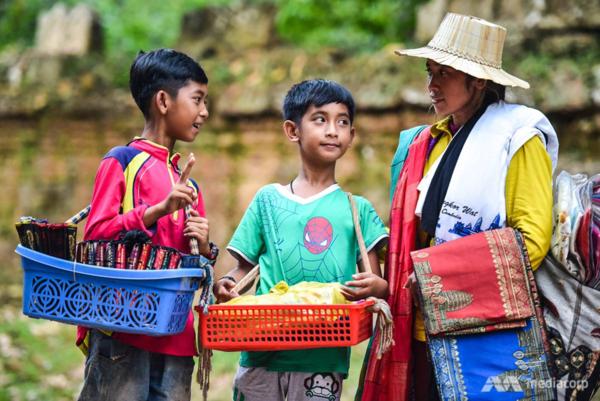 Salik (trái) và em trai Thuch Tithya cùng mẹ bán đồ lưu niệm kiếm sống ở đền Ta Prohm tại Angkor, tỉnh Siem Reap, Campuchia.