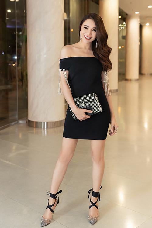 Trà Ngọc Hằng diện chiếc váy đen thanh lịch khoe khéo bờ vai gợi cảm. Cô điểm thêm chiếc ví được đính cườm chỉ có giá 300k.