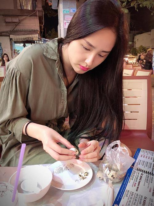 Mai Phương Thúy giản dị ngồi ăn vặt vỉa hè.