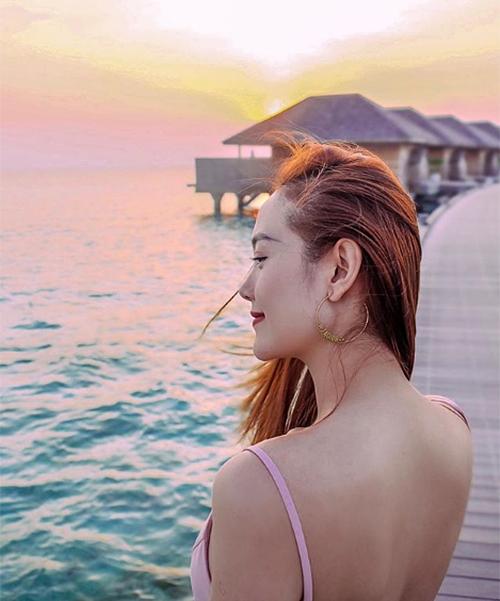 Minh Hằng khoe lưng trần bên biển.