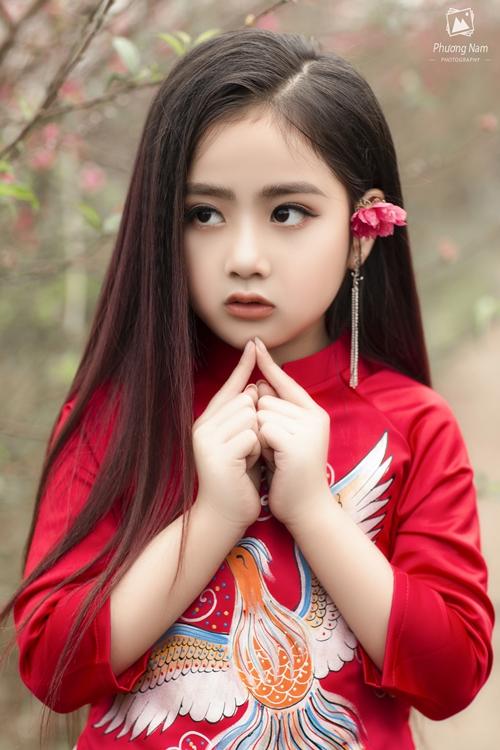 Khoác lên mình bộ áo dài đỏ với hơi hướng hiện đại Nguyễn Lê Khánh Linh (7 tuổi) gây ấn tượng với thần thái kiêu sa, rất giống với nữ diễn viên Triệu Lệ Dĩnh. Sở hữu làn da trắng, gương mặt bầu bĩnh cùng đôi mắt to tròn Khánh Linh xinh xắn, trong sáng trong bộ áo dài.