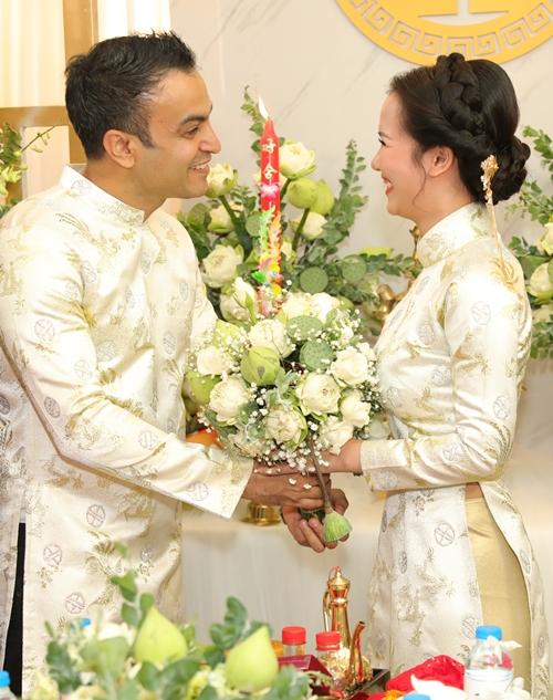 Cô dâu - chú rể xuất hiện rạng rỡ trong trang phục áo dài truyền thống của NTK Nhật Dũng. Chiếc áo dài màu trắng kem kết hợp với chất liệu gấm Phượng Hoàng được dệt hoàn toàn bằng tay tại Lâm Đồng.