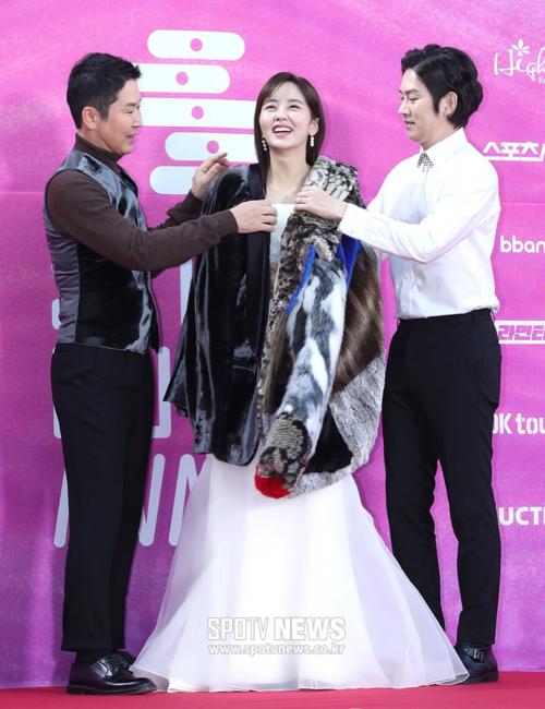 Nữ diễn viên Kim So Hyun đảm nhận vị trí MC của chương trình cùng Shin Dong Yup, Hee Chul (áo trắng). Cô nàng cười tít mắt khi được các anh cởi áo khoác giúp che chắn. So Hyun có phong cách độc lạ, không đụng hàng trên thảm đỏ.