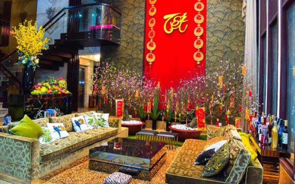 Khắp không gian phòng khách nhà Đàm Vĩnh Hưngđược trang trí bằng câu đối, rượu, cây đào và mâm ngũ quả.
