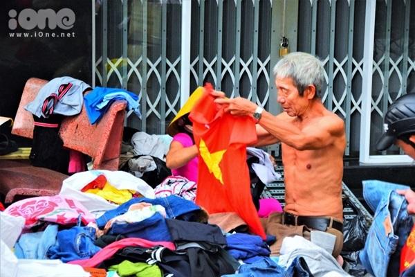 Ông Hiệp, 71 tuổi lựa những chiếc áo tay dài để chống lạnh, vì mỗi ngày ông phải dậy từ sớm để đạp xe đi kiếm củi mót về đun nước lấy hơi để ủi đồ gia công giúp con trai.