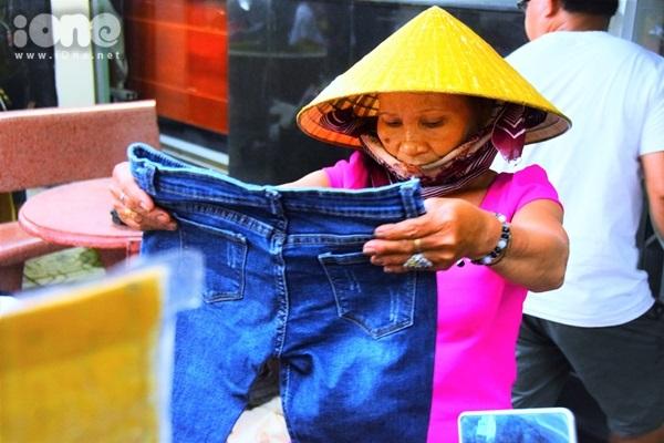 Cô Lê Thị Vui tranh thủ lựa những bộ đồ cho con trai và cháu nội. Nay đã 60 tuổi nhưng hằng ngày cô phải đẩy xe bán bánh bèo để kiếm cơm, nên cả chục năm nay ai cho gì thì mặc nấy chứ cô không biết lựa đồ đẹp là gì.