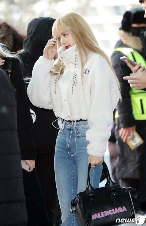 Em út Lisa chính là thành viên có phong cách sành điệu nhất nhóm. Cô nàng giữa ấm với áo bông trắng, quần jean cạp ca khoe đường cong hông và vòng eo nhỏ xíu. Nữ ca sĩ dùng túi xách hàng hiệu để hoàn thành set đồ đắt đỏ.