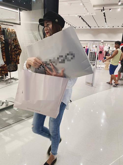 Thanh Hằng như vơ vét cả cửa hàng, hai tay ôm không xuể số quần áo sắm được.