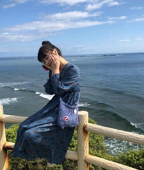Momo khoe ảnh đi chơi Nhật, ngồi hẳn lên bờ rào để tạo dáng trước biển.