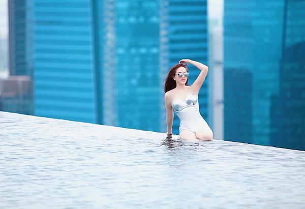 Bảo Thy táo bạo ngồi trên thành bể bơi cao nhất ở Singapore để tạo dáng.