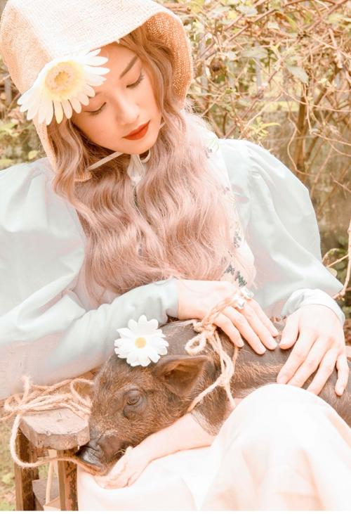 Hoàng Yến Chibi có cách thể hiện kín đáo, ý nhị khi chụp hình cùng heo con. Cô hóa thân thành một cô nàng du mục với biểu cảm ngây thơ, trong sáng.