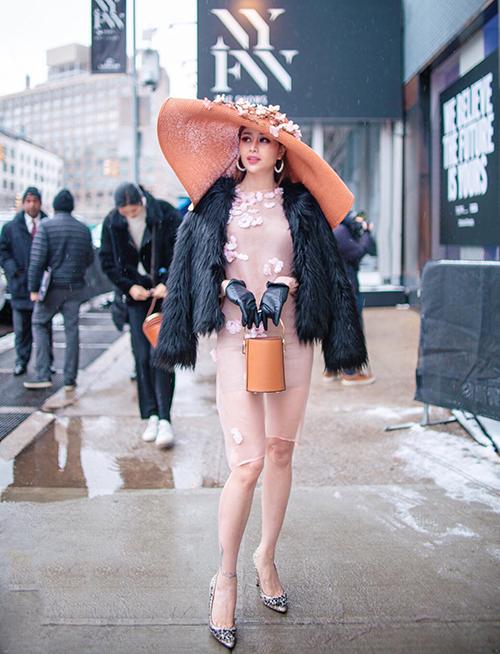 Là khách mời tại New York Fashion Week, Hoa hậu Sella Trương không ngại diện đồ bất chấp thời tiết để có vẻ ngoài thu hút ống kính. Đến dự show của NTK Phương My, người đẹp chơi trội trong bộ váy xuyên thấu mỏng như sương, để chân trần, kết hợp cùng chiếc mũ rộng vành cỡ đại.Sella Trương diện váy xuyên thấu đính hoa do Phương My thiết kế kết hợp với mũ rộng vành. Để giúp vẻ ngoài thêm phần sang trọng, Sella Trương phối thêm với áo lông Moschino và giày Jimmy Choo.