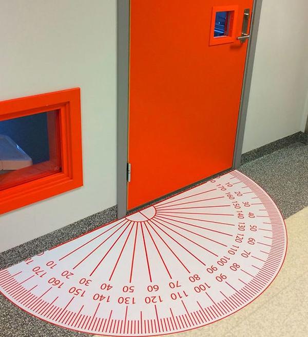 Một cây thước đo góc khổng lồ đặt ngay trước cửa lớp ngầm chứng minh đây là lớp toán học.