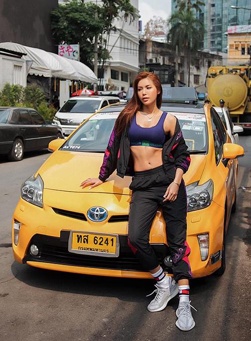 Minh Tú diện đồ sporty khoe eo săn chắcbên chiếc xe taxi màu vàng truyền thống ở Thái Lan.