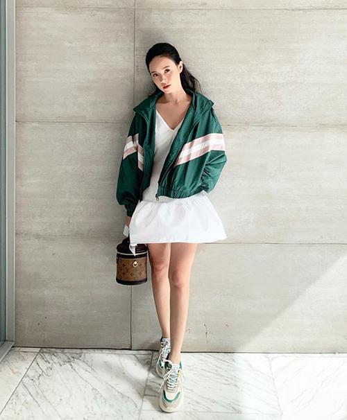 Với chiếc váy trắng và áo khoác thể thao, Midu xinh xắn trông chẳng khác gì teen girl.