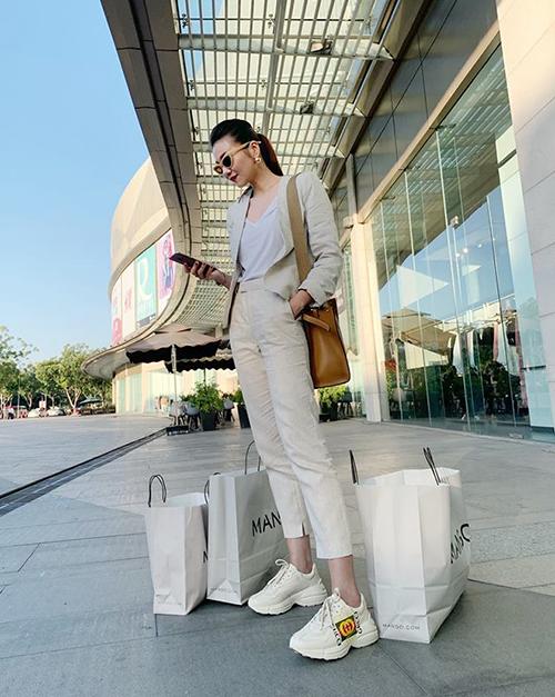 Thanh Hằng diện suit màu trắng sữa, tông xuyệt tông với sneakers để có bộ cánh chất chơi đi shopping.