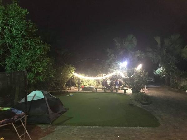Đèn được trang trí lung linh vào buổi tốibên khoảng sân trống của căn nhà vườn. Hoạt động cắm trại, tiệc nướng ngoài trời thường xuyên diễn ra tại đây.
