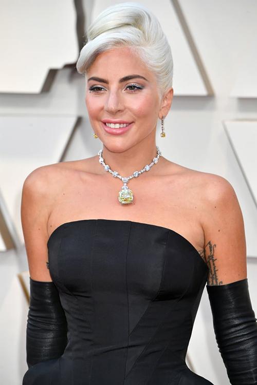 Nổi bật nhất trên trang phục của cô là chiếc vòng cổ thuộc thương hiệu Tiffany&Co. Mặt vòng là viên kim cương Tiffany huyền thoại, nặng tới 128,54 carat và có giá 30 triệu USD (khoảng 700 tỷ đồng). Viên kim cương này được phát hiện từ năm 1877, sau đó đã có 5 lần xuất hiện trong những dịp đặc biệt với các cách chế tác vòng khác nhau.
